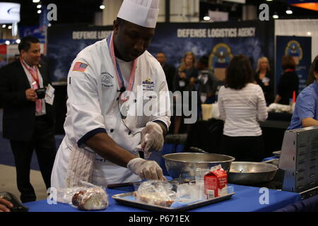 160516-D-IL028-152 NATIONAL HARBOR, Md. (May 16, 2016) U.S. Navy Culinary Specialist (CS1) Eugene Ward from the USS Normandy (CG 60) conducts a cooking demonstration in the Naval Supply Systems Command booth during the 2016 Sea Air Space Expo.  (U. S. Navy by Lee Mundy/Released) - Stock Photo