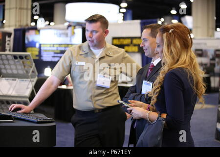 160516-D-IL028-154 NATIONAL HARBOR, Md. (May 16, 2016) AT1 Richard Walsh from U.S. Navy Feet Readiness Center Mid Atlantic, explains the Statistically-driven Maintenance Analysis and Reporting Technology (S.M.A.R.T.) in the Naval Supply Systems Command booth at the 2016 Sea Air Space Expo. (U.S. Navy photo by Lee Mundy/Released) - Stock Photo