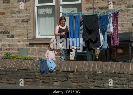 Child helping her mother with the family laundry hanging out to dry  in front garden north of England 2010s UK HOMER SYKES - Stock Photo