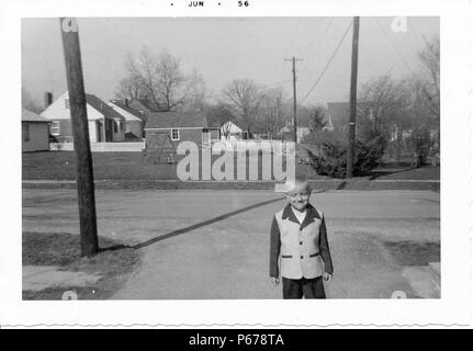 Black and white photograph, showing a young boy, with short blonde hair, facing the camera in three-quarter view, but looking down, wearing a two-toned jacket, with trees and suburban houses visible in the background, likely photographed in Ohio in the decade following World War II, June, 1956. () - Stock Photo