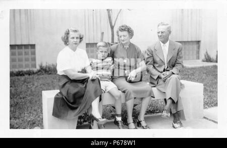 Black and white photograph, showing a woman with short, curly, blonde hair, wearing a skirt and heels, looking seriously at the camera, while sitting on a concrete bench next to a blonde boy wearing a striped shirt and shorts, also wearing a serious expression, with a formally dressed older couple (presumably the boy's grandparents) at right, and a concrete building with glass-block windows visible in the background, likely photographed in Ohio, 1955. () - Stock Photo