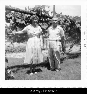 Black and white photograph, showing an older couple, in full length, posing together outdoors, the man, faces the camera, and wears a light colored shirt and trousers, the short-haired woman, wears a light colored, tea-length dress and smiles at something off-camera, her arm rests on a vine-covered fence behind her, likely photographed in Ohio, June, 1956. () - Stock Photo