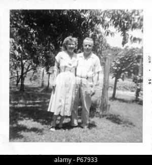 Black and white photograph, showing an older couple, both smiling, standing outdoors in full length, the man wears a light colored shirt and trousers, and wraps his arm around the waist of his wife who wears a light colored, tea-length dress, with foliage visible in the background, likely photographed in Ohio, June, 1956. () - Stock Photo