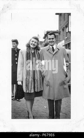 Black and white photograph, showing a well-groomed, smiling man and woman, in full length, facing the camera, the man wearing a light-colored, single-breasted trench coat, and the woman wearing a mid-length coat, with a long fur, stole or lapel, over a two-piece skirt suit, and a string of pearls around her neck, with a second, carefully-coiffed, dark-haired woman in a skirt suit and heeled sandals visible in the background, likely photographed in Ohio in the decade following World War II, 1950. () - Stock Photo