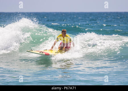 Huntington Beach lifeguard rides a wave on a rescue board on a hot summers day in Southern California USA - Stock Photo