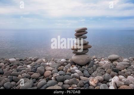 Sea, sky, rocky beach and pyramid of flat gray stones. - Stock Photo