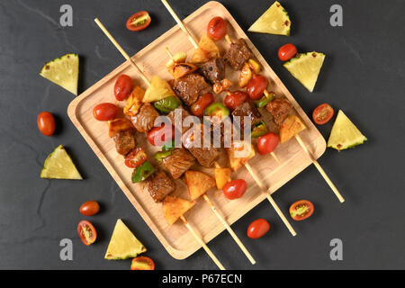 Grill beef barbecue with vegetables in wood plate and on black table, copy space for input text - Stock Photo