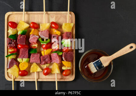 raw beef barbecue with vegetables on wood plate and barbecue sauce - Stock Photo