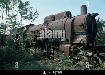 Deep amid the Graveyard at Thessaloniki in Greece an imposing Greek Railway 2-10-0 lies moribund. The design of these locomotives is descended from th - Stock Photo