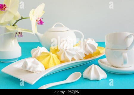 White and yellow meringue on blue background in tea serving with white kettle. - Stock Photo
