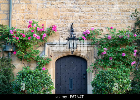 Pink roses around a cotswold stone house front door in the summer. Broadway, Cotswolds, Worcestershire, England - Stock Photo