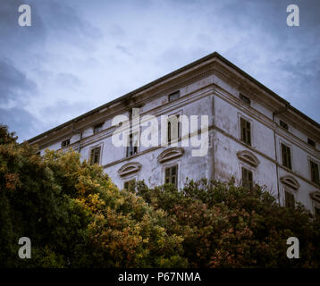 The corner of an old european haunted house / lost place style mansion with broken windows surrounded by trees under a twilight sky. - Stock Photo