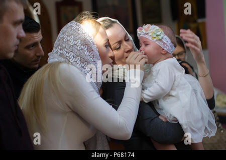 Belarus, Gomel, 25 March. 2018. The Prudhkovsky Church.Mother and godmother on a baptismal rite.Parents with a child in the church at the ceremony of  - Stock Photo