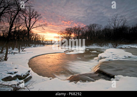 The chilly water of Prairie Creek flows over a waterfall as the sun sets on a winter day.  Des Plaines Conservation Area, Will County, Illinois, USA. - Stock Photo