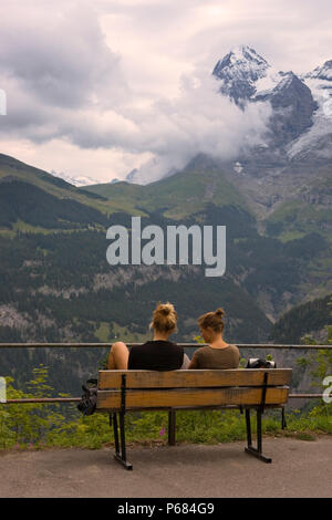 Two girls admire the view from Mürren of the Lauterbrunnen valley and the Mönch beyond, Bernese Oberland, Switzerland - Stock Photo