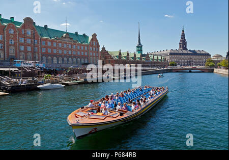 Canal cruise boat in Slotsholm Canal in Copenhagen.Christiansborg Castle, the Parliament, the old stock exchange and dockside cafe and kayak rental. - Stock Photo