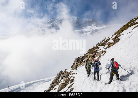 The summit of Mt Rainier looms above clouds. Climbers and hikers on the Skyline trail, Mount Rainier National Park, Washington, USA. - Stock Photo