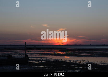 A burst of orange during sunset from Seasalter on the North Kent coast looking across the Swale Estuary towards the Isle of Sheppey. - Stock Photo