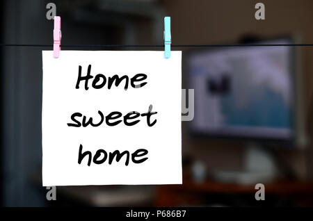 Home sweet home. Note is written on a white sticker that hangs with a clothespin on a rope on a background of office interior . - Stock Photo