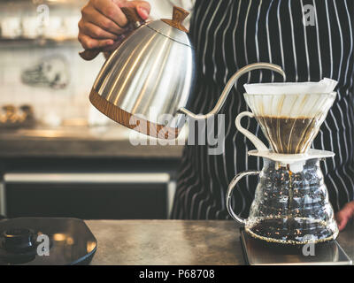 Barista Brewing Drip Coffee, Hand Pouring Hot Water from The Kettle over The Coffee Powder. - Stock Photo