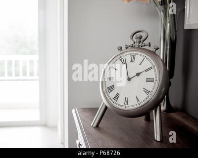 Stainless Classic Vintage Roman Numerals Clock. Still Life on Wooden Cabinet in White Room. - Stock Photo
