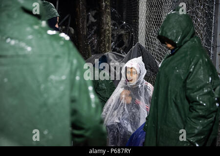 People wearing plastic ponchos sit under the rain as they wait at the makeshift refugee camp  of the Greek-Macedonian border near the Greek village of - Stock Photo
