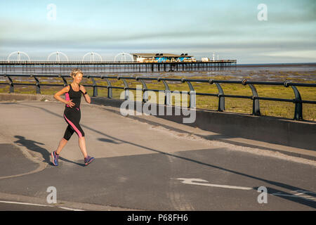 Southport, Merseyside, 29th Jun, 2018. UK Weather. Sunny but hazy start to the day as a smoke clouds drifts over the resorts pier. Overnight a 2nd moorland wildfire at Winter hill near Bolton has caused problems for fire-fighters with smoke drifting eastwards in light winds over the north-west of England. Credit: MediaWorldImages/AlamyLiveNews. - Stock Photo