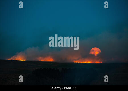 Winter Hill, Greater Manchester, UK. 28th Jun, 2018. The moon rises over a grass fire on the moorlands of Winter Hill, near Bolton in Greater Manchester. Credit: Jason Smalley Photography/Alamy Live News - Stock Photo