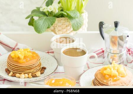 Perfect breakfast for 2. Tray with pancakes with orange jam and nuts on vintage plates and 2 white coffee cups - Stock Photo