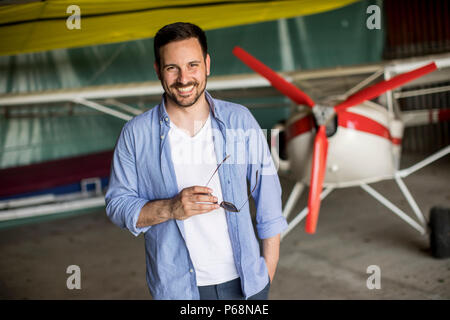 Handsome young man in the airplane hangar - Stock Photo