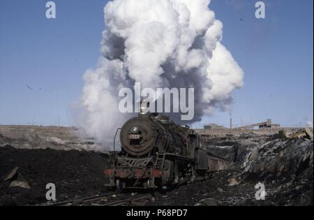 The vast opencast coal mine at Manzhouli in Inner Mongolia on the Russian border in north east China. The coal and spoil is bought out by steam trains - Stock Photo