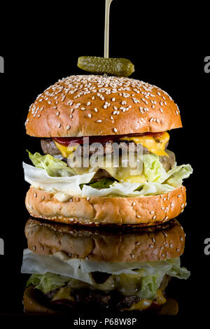 California Love Burger - Patties grilled in mustard, onion reduction and double American cheese slice with reflection isolated on black background - Stock Photo