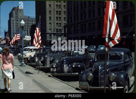 Street in Lincoln, Nebraska, USA showing a line of cars parked in front of several American flags - Stock Photo