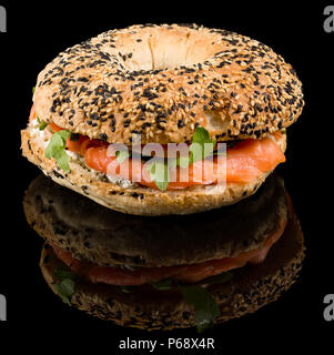 Smoked Salmon Bagel - Fresh baked bagel, cream cheese topped with smoked salmon and red onions with reflection isolated on black background - Stock Photo