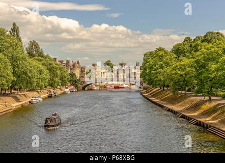 A view down the River Ouse towards Lendal Bridge and the City skyline.  Boats line the left bank with trees on either side. - Stock Photo