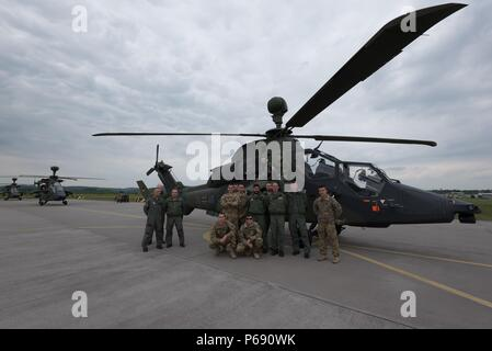 Pilots from Kampfhubschrauberregiment 36 'Kurhessen,' and from 1st Battalion, 3rd Aviation Regiment, 12th Combat Aviation Brigade pose in front of a Tiger Attack Helicopter during exercise Strong Punch on Fritzlar Air base near Fritzlar, Germany, May 19, 2016. Strong Punch is an exercise laboratory in which German and American aviators can evaluate and refine the effectiveness of their current tactics, techniques and procedures (TTP's) in a threat environment that consists of real world, modern electronic warfare platforms (EW) and reconnaissance surveillance equipment. - Stock Photo