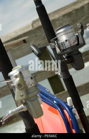 Fishing rod and reel stands on pier at Myrtle Beach State Park, SC, USA. - Stock Photo