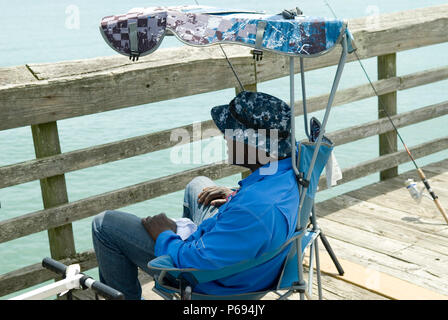 Man relaxes in chair on pier at Myrtle Beach State Park, SC, USA. - Stock Photo