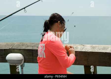 Woman baits hook for fishing on pier at Myrtle Beach State Park, SC, USA. - Stock Photo