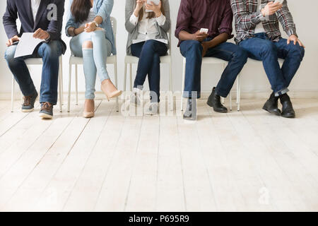 Bottom view of diverse work candidates waiting for job interview - Stock Photo