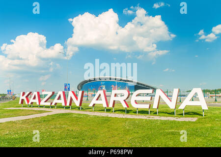 KAZAN, RUSSIA - 25 JUNE, 2018: View of Kazan Arena stadium with big sign on green grass in foreground and stadium building with big screen in backgrou - Stock Photo