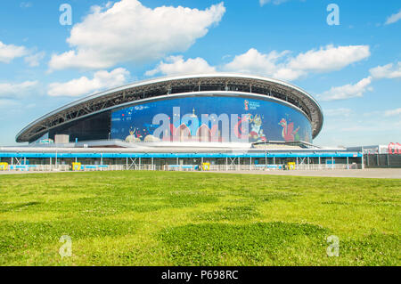 KAZAN, RUSSIA - 25 JUNE, 2018: Kazan Arena stadium with green grass in foreground and FIFA 2018 symbol Zabivaka on big screen. - Stock Photo