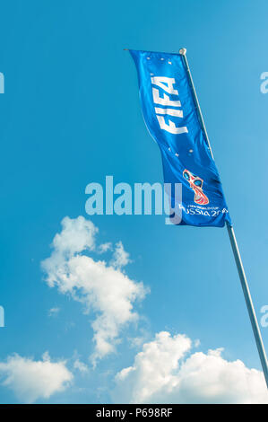 KAZAN, RUSSIA - 25 JUNE, 2018: FIFA world cup flag flying on flag pole against clear blue sky with white clouds near Kazan Arena stadium. - Stock Photo