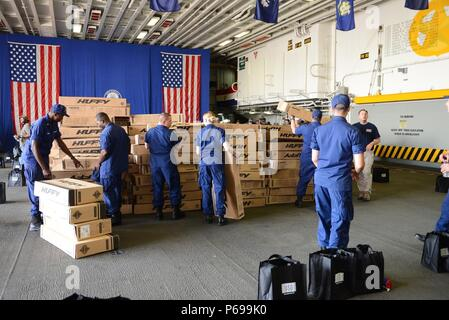 160525-N-YD083-305 NEW YORK (May 25, 2016) – Coast Guardsmen stack boxes of bikes in the hangar bay of the amphibious assault ship USS Bataan (LHD 5) in preparation for the USO Build-A-Bike Program during 2016 Fleet Week New York (FWNY). FWNY, now in its 28th year, is the city's time-honored celebration of the sea services. It is an unparalleled opportunity for the citizens of New York and the surrounding tri-state area to meet Sailors, Marines and Coast Guardsmen, as well as witness firsthand the latest capabilities of today's maritime services. The weeklong celebration has been held nearly e - Stock Photo