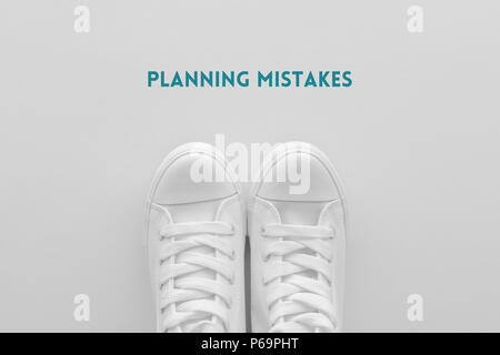 Planning mistakes concept, young person in white sneakers standing over the text imprint - Stock Photo