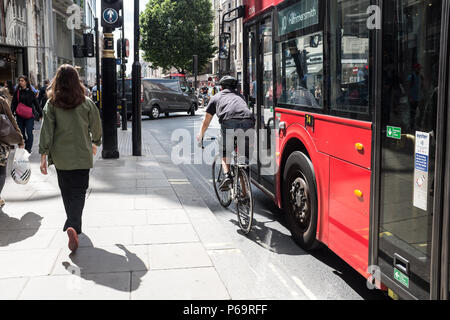 A cyclist waits for green light in a traffic in London, the capital of England and the United Kingdom London is an importantglobal city in the arts,  - Stock Photo