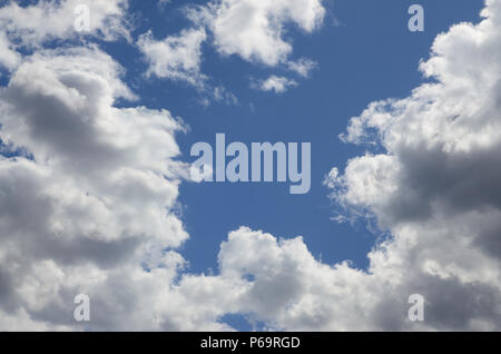 The blue sky with a lot of white clouds of different sizes, forming a frame around the cloudless area . - Stock Photo