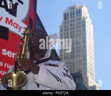 NEW YORK (May 29, 2016) - Musician 1st Class Winnie Dawkins from Nassau, Bahamas, belts a saxophone solo during a performance in the center of Times Square. Dawkins performed along with other members of US Fleet Forces Brass Band while in town for Fleet Week New York. More than 4,500 Sailors, Marines and Coast Guardsmen from 14 vessels including the Royal Canadian Navy descended upon the city for FWNY, now in its 28th year, to interact with the citizens of New York and the tri-state area, enhancing public awareness of today's maritime services. #FleetWeekNYC #USNavy #NAVINFOEast #USFleetForces - Stock Photo