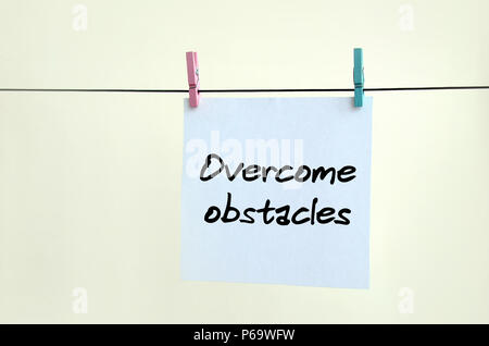 Overcome obstacles. Note is written on a white sticker that hangs with a clothespin on a rope on a background of beige wall . - Stock Photo