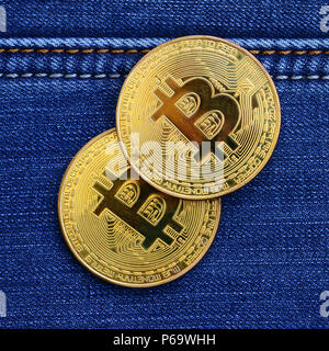 Two golden Bitcoins is lies on a blue jeans fabric. New virtual money. New crypto currency in the form of the coins . - Stock Photo